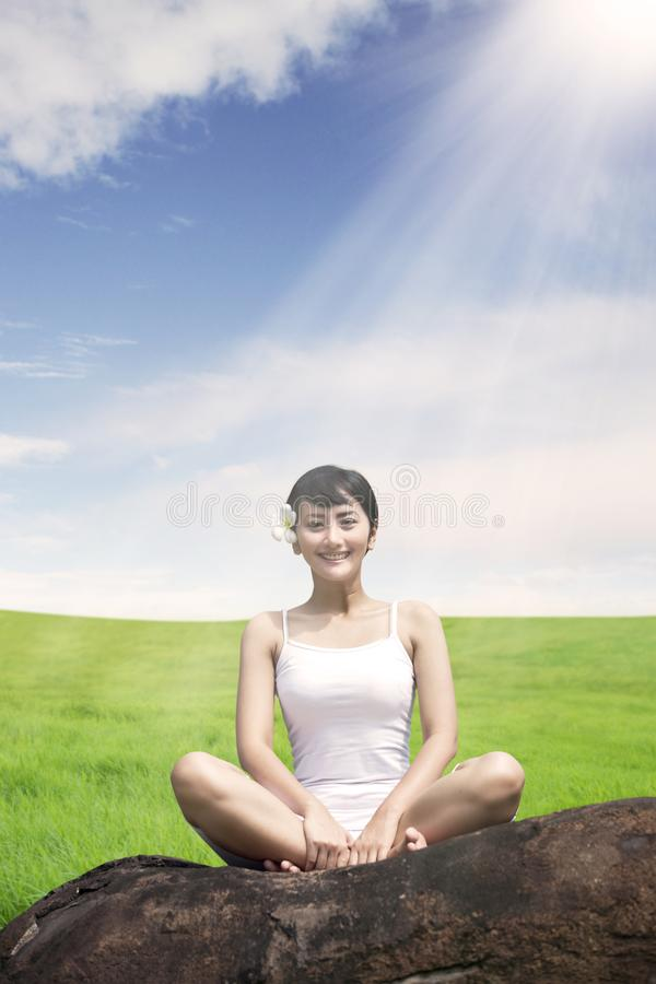 Asian woman meditating outdoors on the rock at meadow against blue sky royalty free stock image