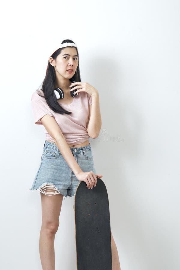 Beautiful asian girl holding skateboard stock photo