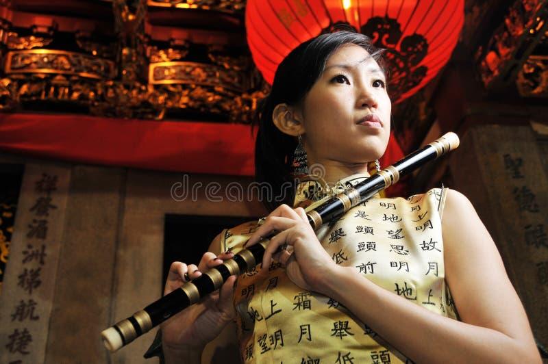 Beautiful Asian Woman Playing Flute Stock Image