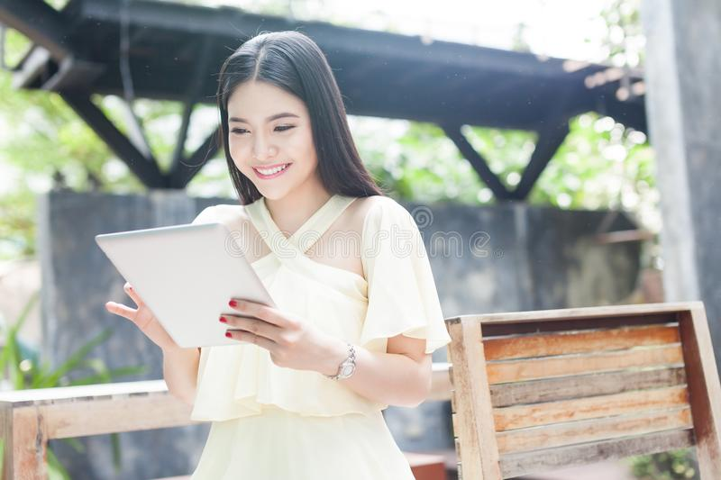 Beautiful Asian woman playing with her tablet stock images