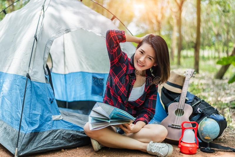 Beautiful Asian woman playing Ukulele in front of camping tent in pine woods. People and Lifestyles concept. Adventure and Travel royalty free stock photos