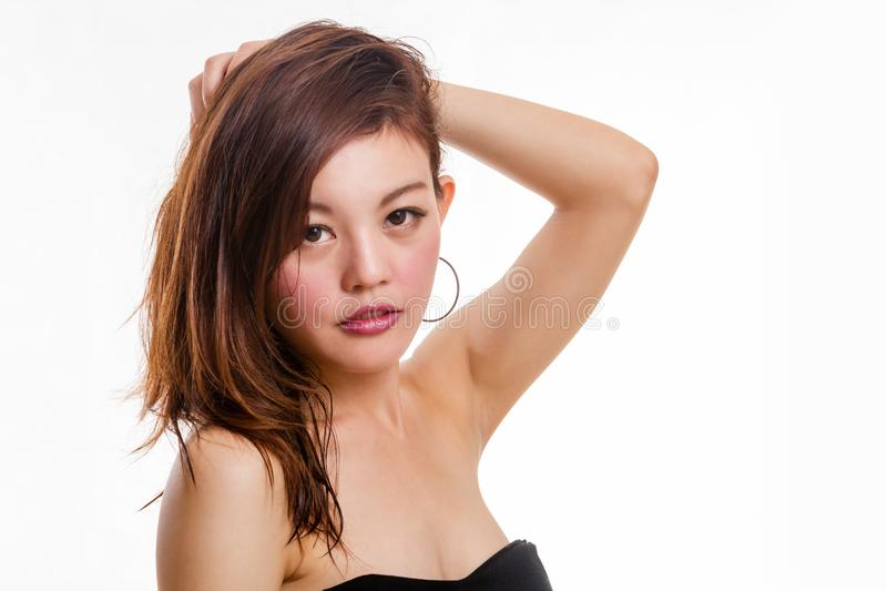 Beautiful Asian woman plays with hair stock image