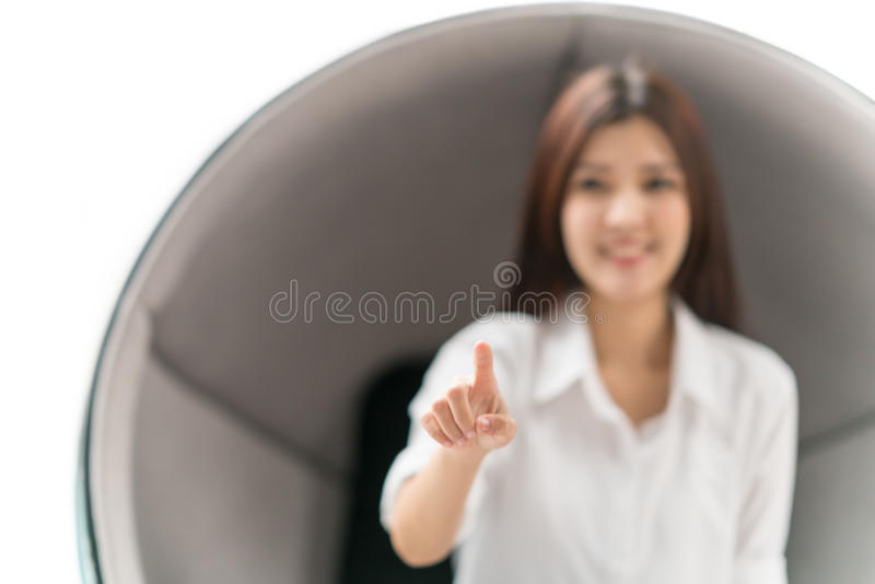 Beautiful Asian woman pointing forward to screen, sit on modern round chair on white background. Graphic resource for business, health, education, lifestyle stock photos