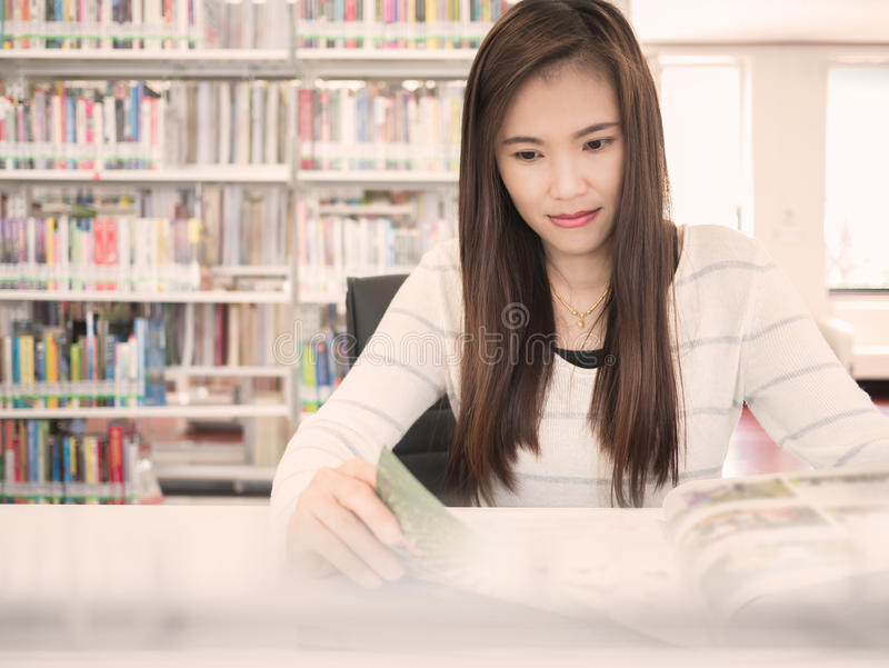 A beautiful asian woman reading a magazine in library. royalty free stock photo
