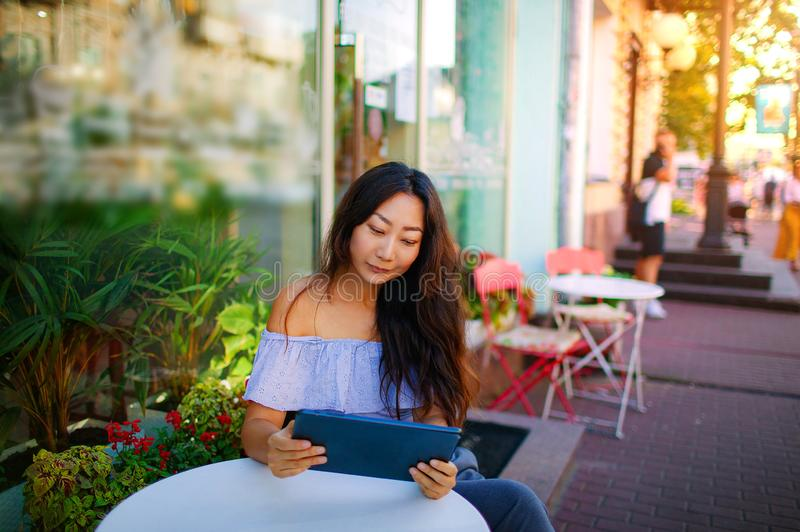 Beautiful asian woman reading a magazine online on tablet at coffee cafe. royalty free stock photography