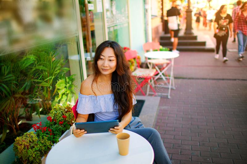 Beautiful asian woman reading a magazine online on tablet at coffee cafe. stock photography