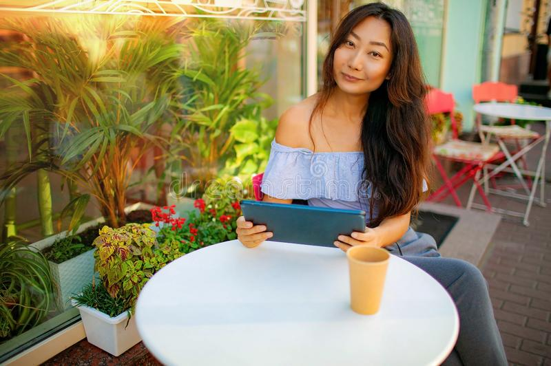 Beautiful asian woman reading a magazine online on tablet at coffee cafe. stock images