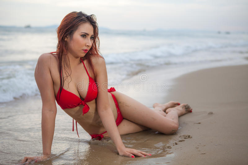 Beautiful asian woman in red bikini posing royalty free stock photo