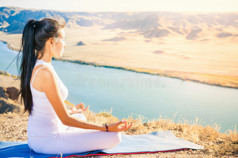 Beautiful asian woman relaxing and meditating outdoor at mountai royalty free stock photography