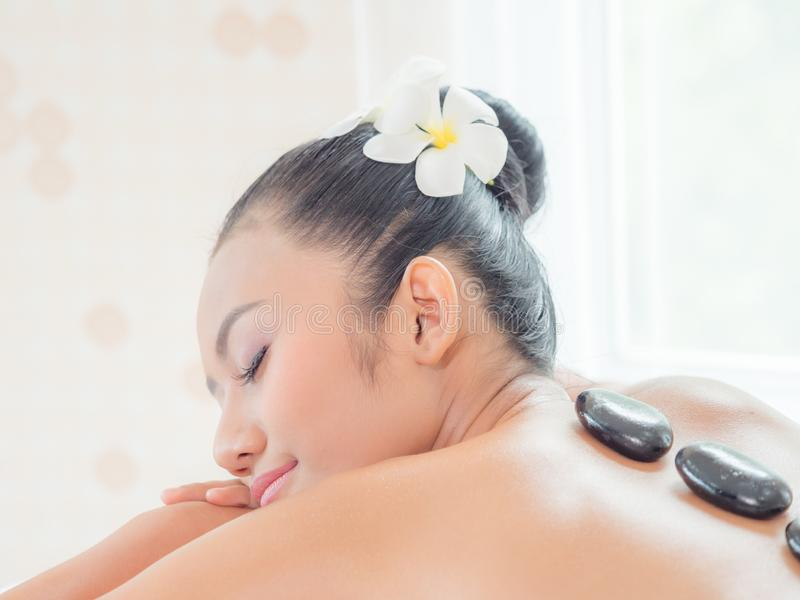 A beautiful Asian woman is relaxing in a spa shop when an expert masseuse places a hot stone on her back royalty free stock photography