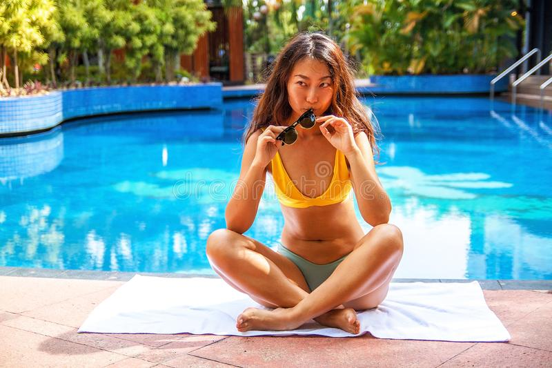 Beautiful asian woman relaxing in swimming pool in the hotel. royalty free stock photo