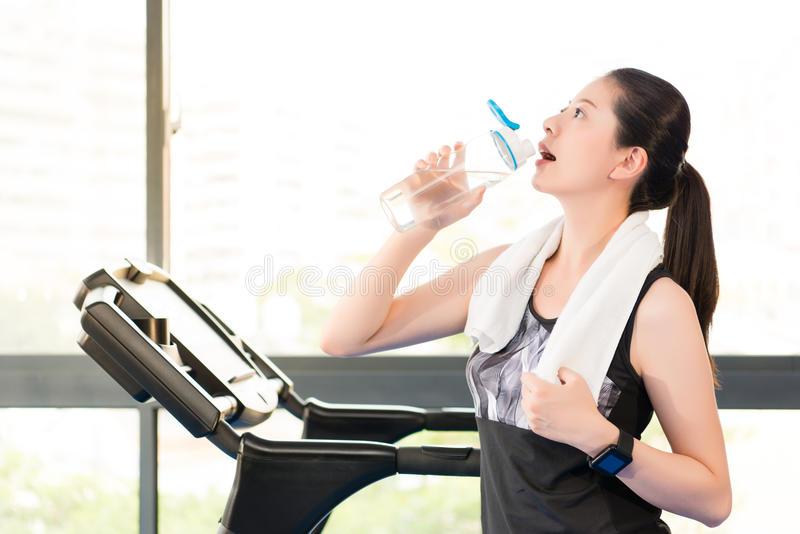 Beautiful asian woman rest drinking water bottle after treadmill. Beautiful asian woman take rest drinking water bottle after run treadmill. indoors gym stock photography