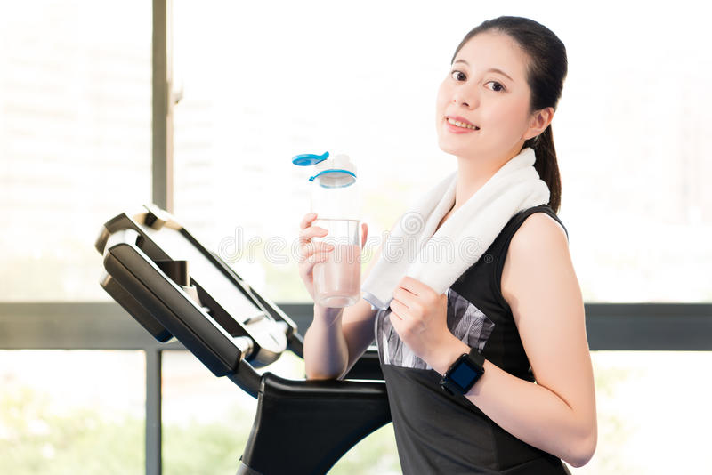 Beautiful asian woman rest holding water bottle after treadmill. Beautiful asian woman take rest holding water bottle after run treadmill. indoors gym background stock photo