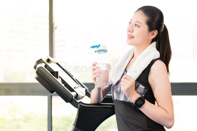 Beautiful asian woman rest holding water bottle after treadmill. Beautiful asian woman take rest holding water bottle after run treadmill. indoors gym background royalty free stock photos