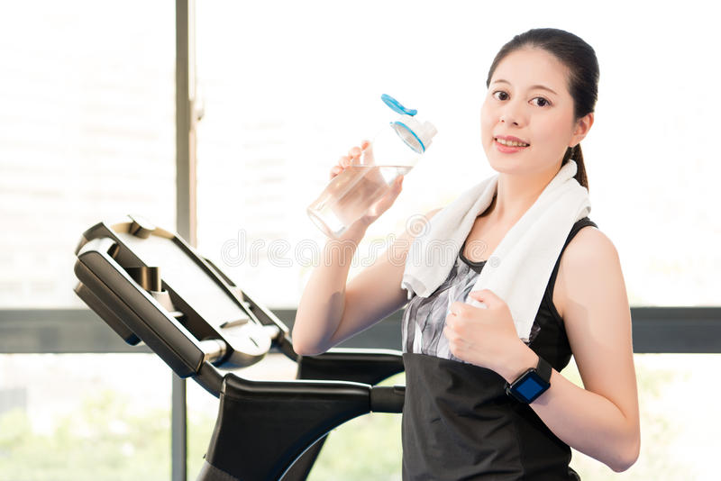 Beautiful asian woman rest holding water bottle after treadmill. Beautiful asian woman take rest holding water bottle after run treadmill. indoors gym background royalty free stock photography
