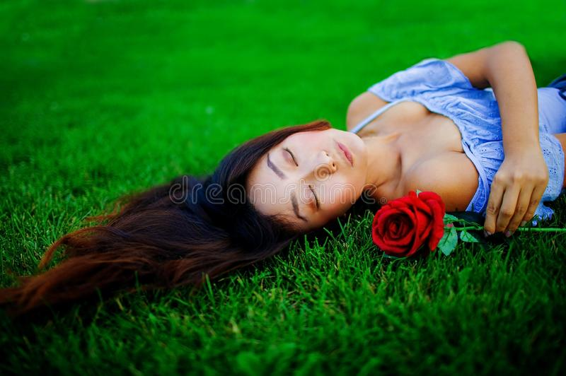 Beautiful asian woman with rose in nature. Beauty woman with long hair relax on green grass. royalty free stock image