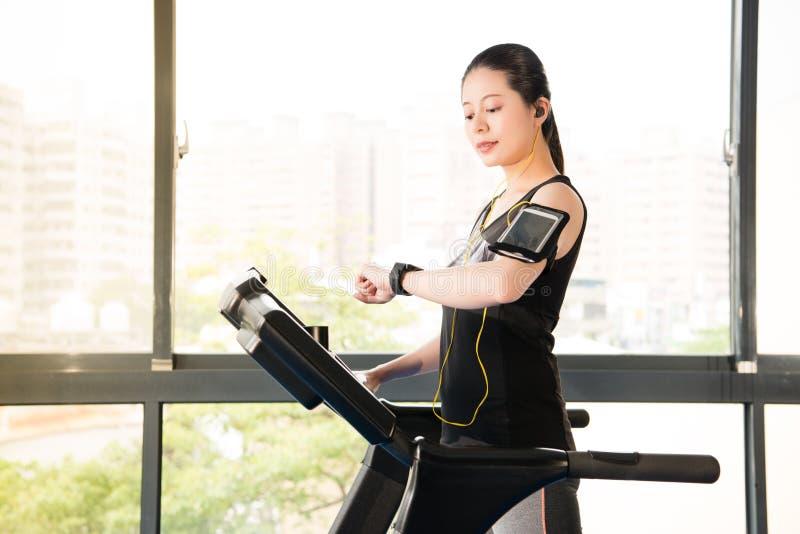 Beautiful asian woman running treadmill use smartphone listening. Beautiful asian woman running treadmill use smartwatch connect smartphone listening music stock photo