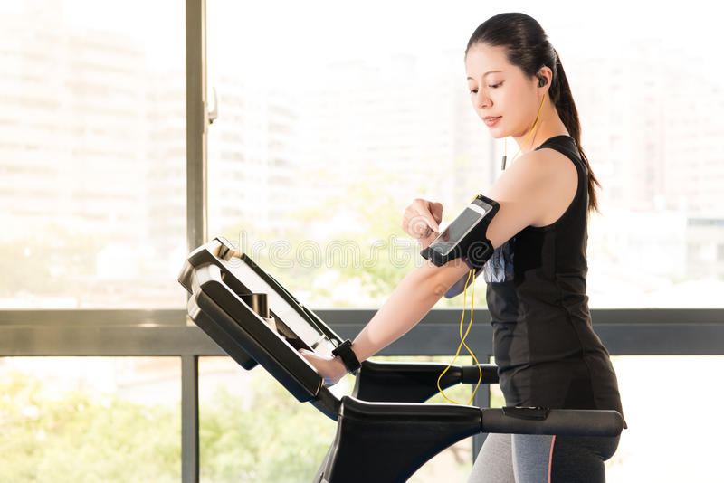Beautiful asian woman running treadmill use smartphone listening. Beautiful asian woman running treadmill use smartwatch connect smartphone listening music royalty free stock photo