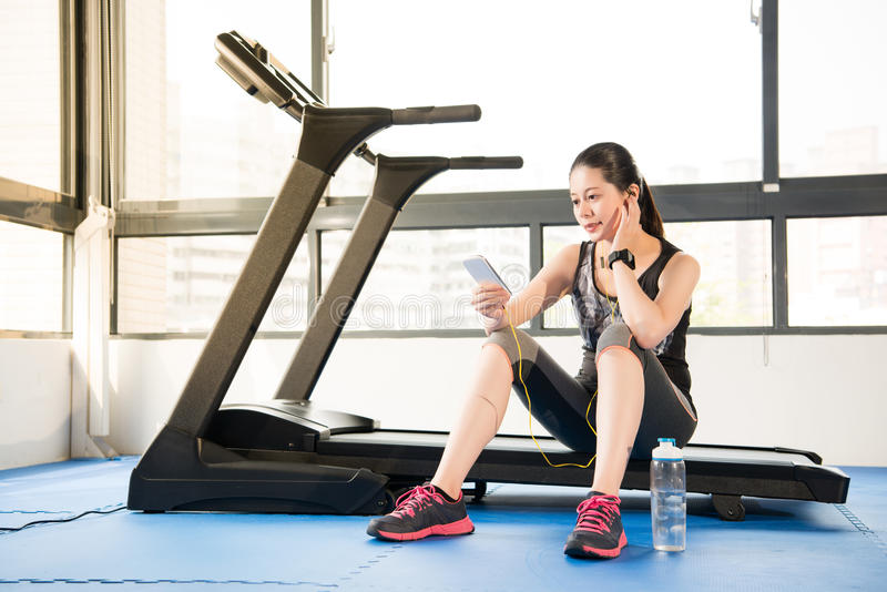 Beautiful asian woman running treadmill use smartphone listening. Beautiful asian woman running treadmill use smartwatch connect smartphone listening music stock images