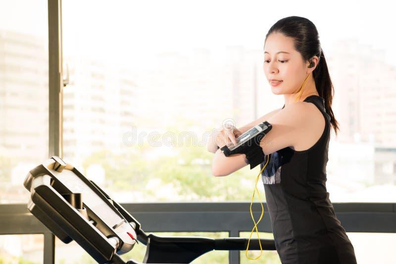 Beautiful asian woman running treadmill use smartphone listening. Beautiful asian woman running treadmill use smartwatch connect smartphone listening music royalty free stock photos