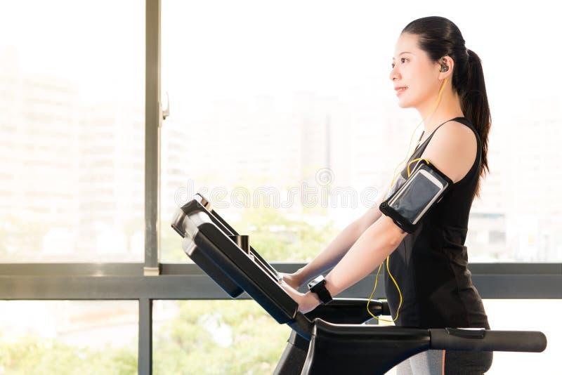 Beautiful asian woman running treadmill use smartphone listening. Beautiful asian woman running treadmill use smartwatch connect smartphone listening music royalty free stock photography