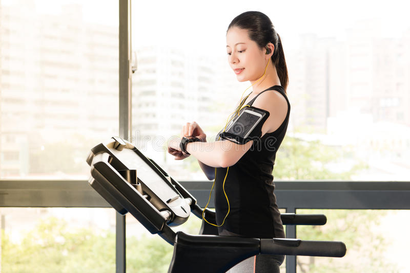 Beautiful asian woman running treadmill use smartwatch listening. Beautiful asian woman running treadmill use smartwatch connect smartphone listening music royalty free stock images
