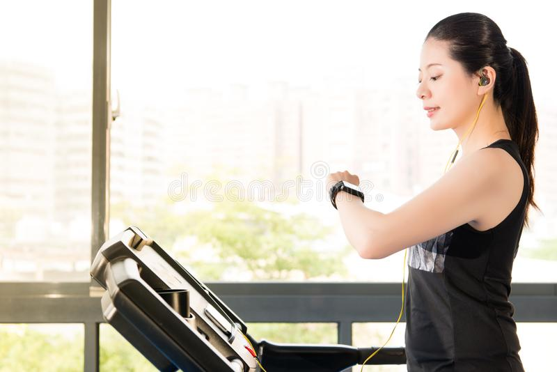 Beautiful asian woman running treadmill use smartwatch listening. Beautiful asian woman running treadmill use smartwatch connect smartphone listening music stock images