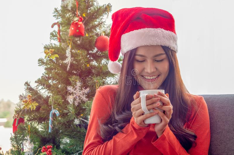 Beautiful Asian woman in a Santa Claus hat is sitting on the sofa, holding a white cup and happy to drink hot tea, hot coffee. royalty free stock images