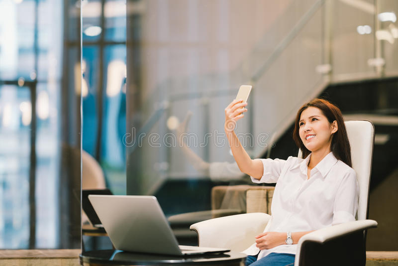 Beautiful Asian woman selfie or VDO call on smartphone. Working with laptop, in office or living room. Modern lifestyle with gadget technology or casual royalty free stock photo