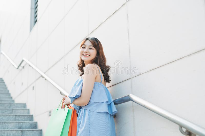 Beautiful Asian woman with shopping bags on stairs outdoors. Shopping concept stock photography