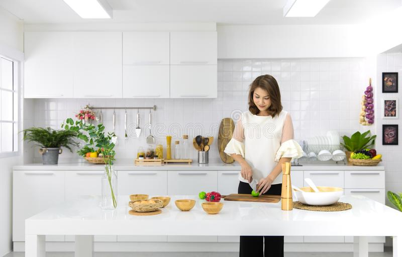 Beautiful Asian woman showing her new kitchen decoration and play with fake fruits and vegetables. Concept to modern housewife royalty free stock photo