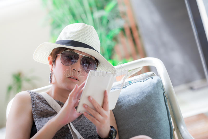 Beautiful asian woman sitting on the chair and reading a text me stock photo