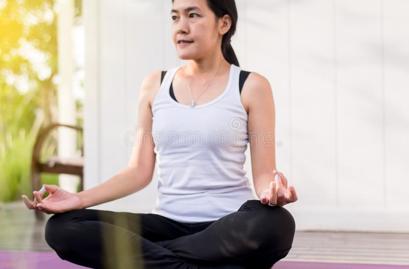 Beautiful asian woman sitting practicing doing yoga meditating after waking up at home,Healthy and lifestyle concept stock photos