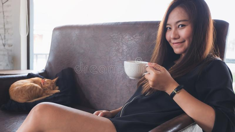 A beautiful Asian woman sitting on sofa while a little brown cat is sleeping on a black pillow. Closeup image of a beautiful Asian woman sitting on sofa while a royalty free stock image