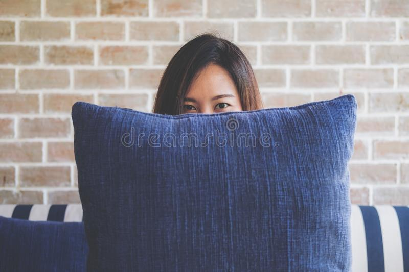 A beautiful Asian woman sitting on sofa and playing with a big blue pillow to cover her face with feeling happy and relax in cafe stock photography