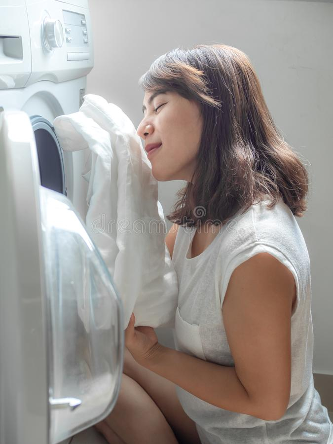Beautiful Asian woman smelling white clean linen shirt after washing from washing machine royalty free stock photography