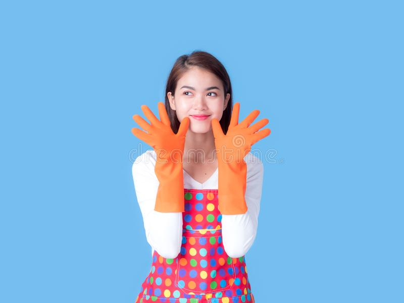A beautiful Asian woman smiles and raises her hand, pretending to be cleaning the house. Which is her favorite job, accessory, adult, apron, attractive royalty free stock photography