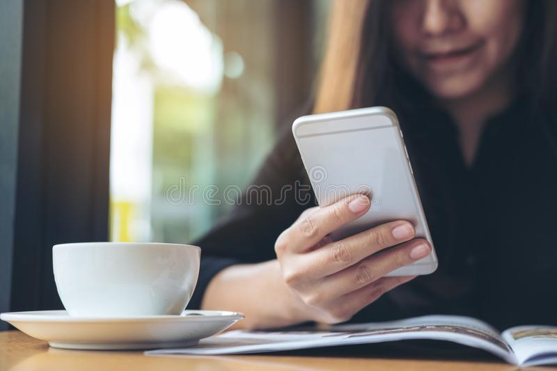 A beautiful Asian woman with smiley face holding and using smart phone while reading magazines with coffee cup on wooden table stock photography