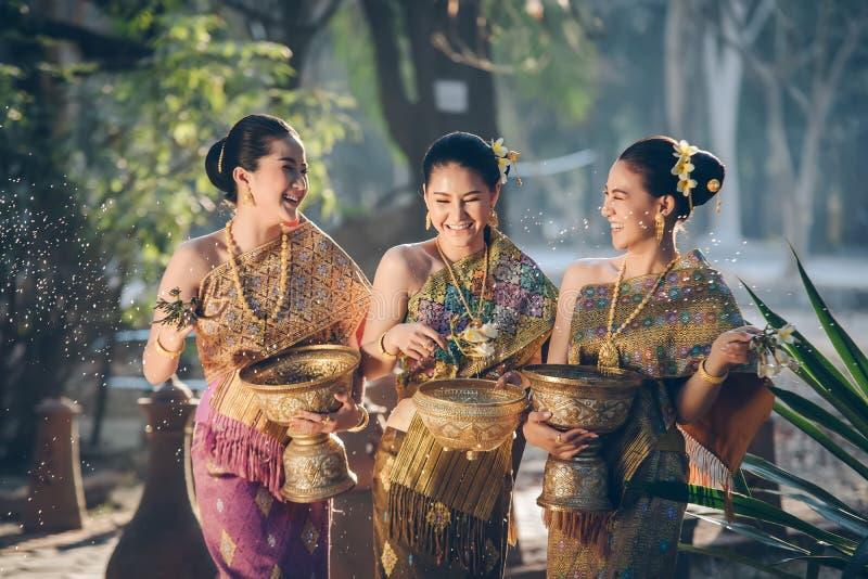 Beautiful Asian woman splashing water during tradition festival Thai. Beautiful Asian women splashing water during tradition festival Thai,Songkran festival royalty free stock photo