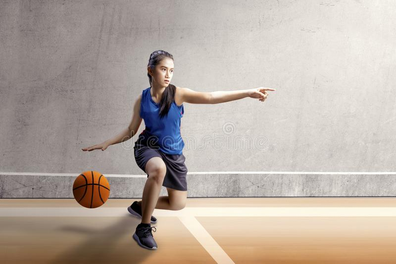 Beautiful asian woman in sport jersey dribbling the basketball with left arm pointing in the basketball court. With wooden floor and concrete wall background royalty free stock images