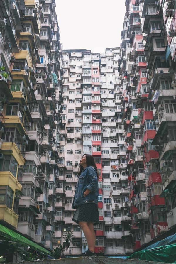 Beautiful asian woman standing among the crowded residential building of the community in Quarry Bay, Hong Kong. A beautiful asian woman standing among the stock images