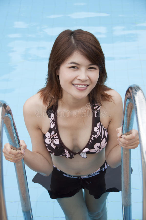 Beautiful Asian woman in swimming pool. royalty free stock images