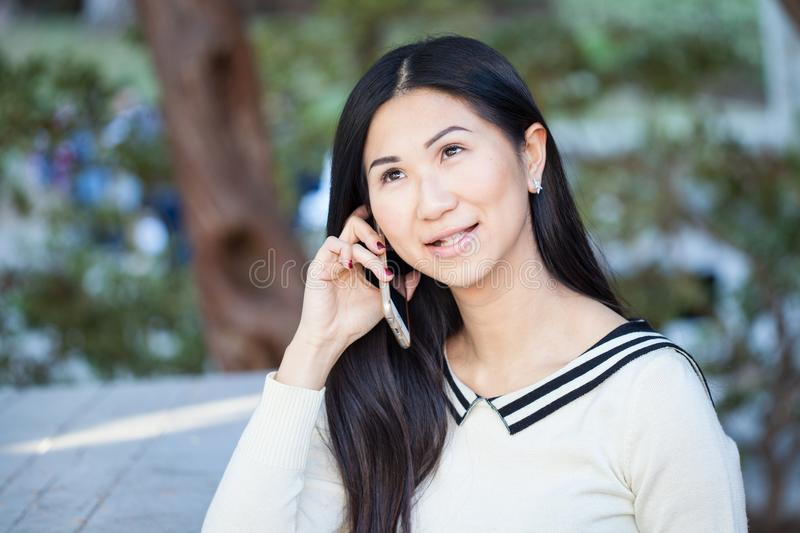 Beautiful Asian woman talking on the phone with a smile on her f stock photo