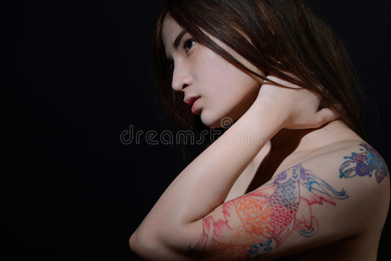Beautiful asian woman with a tattoo on her arm and shoulder,dark background. Beautiful asian woman with tattoo on her arm and shoulder,dark background royalty free stock image