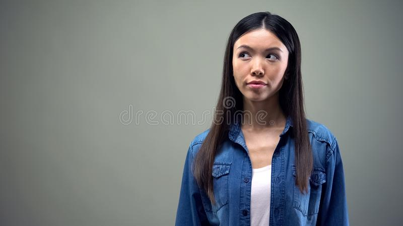 Beautiful asian woman thinking, looking aside, isolated on grey background. Stock photo royalty free stock photo