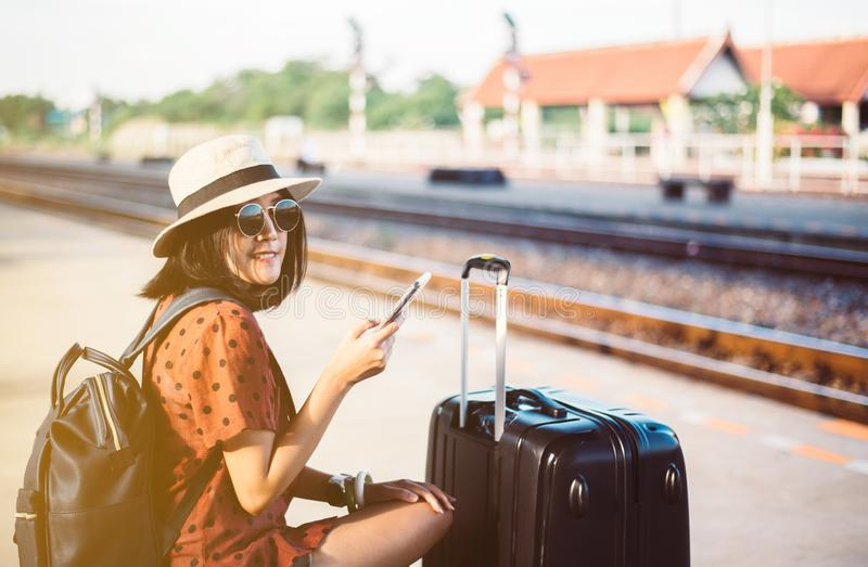 Beautiful asian woman tourist  using mobile phone and waiting train at train station,Travel and vacation concept stock photo