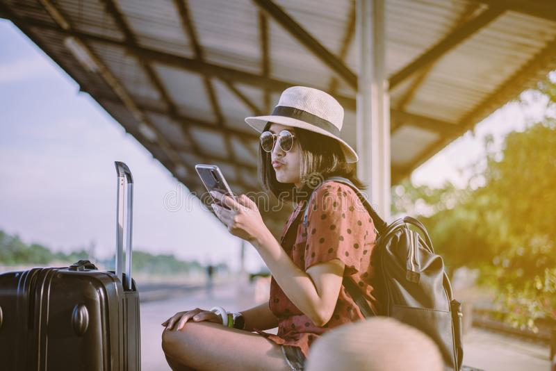 Beautiful asian woman tourist  using smart phone and waiting train at train station,Travel and vacation concept stock image