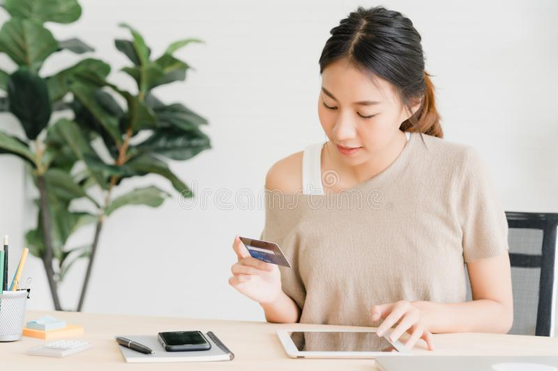 Beautiful Asian woman using smartphone buying online shopping by credit card in living room at home. stock photos