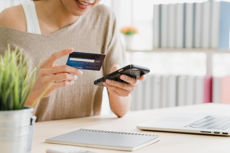 Asian woman using smartphone buying online shopping by credit card while wear sweater sitting on desk in living room at home. Beautiful Asian woman using stock image