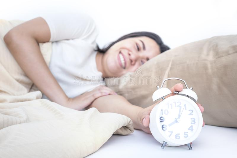 Beautiful asian woman waking up in her bed and she smiling adequate rest, sleeping concept royalty free stock photography